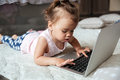 Little child girl lies on bed indoors using laptop computer