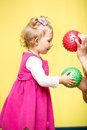 Little child girl playing with ball in kindergarten montessori preschool class Stock Photos