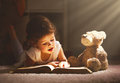 Little child girl is reading a book in evening in dark with a to Royalty Free Stock Photo