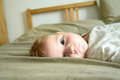 Little child with intent look lying on the bed Royalty Free Stock Photo