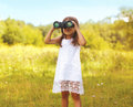 Little child looks in binoculars outdoors in sunny summer day Royalty Free Stock Photo