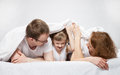 Little child lying in the bed between her parents neutral background Stock Image