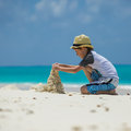 Little child making sand castles at the beach boy castle Stock Photography