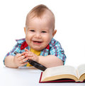 Little child play with book and magnifier Royalty Free Stock Photo