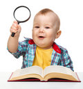 Little child play with book and magnifier Royalty Free Stock Photography