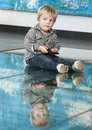 Little child playing with cellphone and his reflexion on the floor cute Stock Image