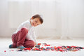 Little child playing with lots of colorful plastic blocks indoor Royalty Free Stock Photo
