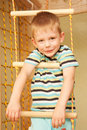 Little child playing sports at sport center kid climbing on a rope ladder Stock Images