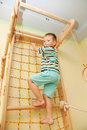 Little child playing sports at sport center kid climbing on a rope net bottom view Royalty Free Stock Photography