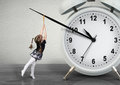 Little child pulling hand clock, time management concept Royalty Free Stock Photo