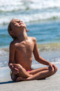 Child yoga relaxing beach ocean Royalty Free Stock Photo