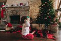 Little child sitting on the floor near the Christmas tree in the Royalty Free Stock Photo