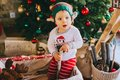 Little child sitting on the floor near the Christmas tree Royalty Free Stock Photo