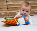 Little child with special baby book explores by tasting it Royalty Free Stock Image