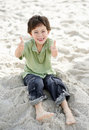Little child with two thumbs up at the sea shore Stock Photos