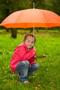 Little child under orange umbrella Stock Images