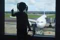 Little child waiting for boarding to flight in airport terminal silhouette of baby girl her transit hall and looking at airplane Stock Photography