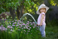 Little child watering onions in the garden Royalty Free Stock Photo