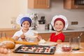 Little children holding dough and pulling apart brother sister having fun at kitchen table Royalty Free Stock Images