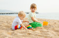 Little children playing with sand two beautiful girls play on the beach Stock Photography