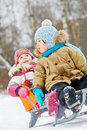 Little children sit in sled in winter park focus on first child Royalty Free Stock Photo
