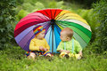 Little children under colorful umbrella cute outdoors Stock Image