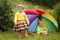 Little children under colorful umbrella cute outdoors Stock Images