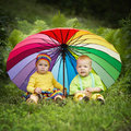 Little children under colorful umbrella cute outdoors Stock Photography