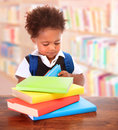 Little clever preschooler in the library reading books cute african boy preparing to go to first class enjoying study elementary Royalty Free Stock Images