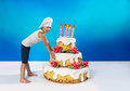 Little confectioner drags a cake big Stock Images