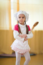 Little cook girl wearing chef s hat with big wooden spoon Stock Photo