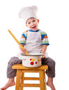 Little cook with ladle and pan smiling sitting on the stool isolated on white Royalty Free Stock Photo