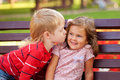 Little couple in love outdoor kids concept boy kissing girl Stock Photography
