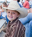 Little cowboy with a dirty face cute sits in crowd of people watching rodeo in northern idaho Stock Images