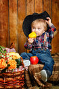 Little cowboy on a farm in a hat and jeans after harvest Royalty Free Stock Images