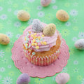 Little cupcake on green with frosting and colorful easter eggs Royalty Free Stock Images