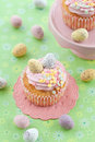 Little cupcake on green with frosting and colorful easter eggs Stock Photos