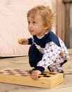 Little curly boy holds a chess-board Royalty Free Stock Photos