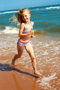 Little curly cheerful girl runs along the shore of the ocean on