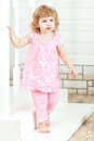 Little curly girl in a pink dress and bare feet coming out of the house and go down the stairs Royalty Free Stock Photo