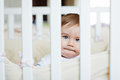 Little cute adorable little blond boy in a striped bodykit sitti Royalty Free Stock Photo