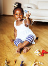 Little cute african american girl playing with animal toys at ho