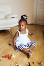 Little cute african american girl playing with animal toys at home, pretty adorable princess in interior happy smiling Royalty Free Stock Photo
