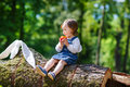 Little cute baby girl eating fruit in forest summer Royalty Free Stock Image