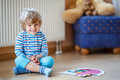 Little cute blond boy playing with puzzle game at home funny of two years kid having fun indoors child development concept Royalty Free Stock Photos
