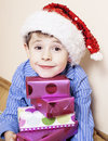 Little cute boy with Christmas gifts at home. close up emotional face on boxes in santas red hat Royalty Free Stock Photo