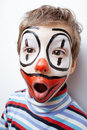 Little cute boy with facepaint like clown pantomimic expressions close up Stock Photo