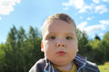 Little cute boy looks at camera outdoor Royalty Free Stock Photo