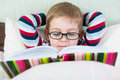 Little cute boy reading book in bed glasses Royalty Free Stock Photography