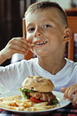 Little cute boy 6 years old with hamburger and Royalty Free Stock Photo